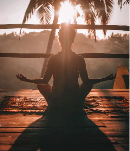 woman doing Vinyasa yoga at sunset